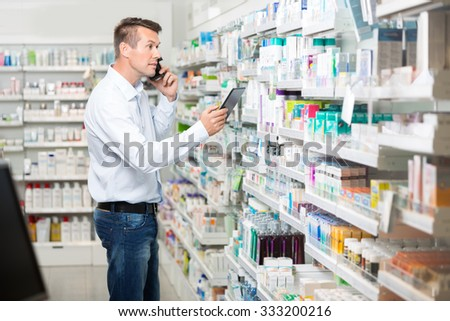 Mid adult male customer using mobile phone and digital tablet while looking at products in pharmacy - stock photo