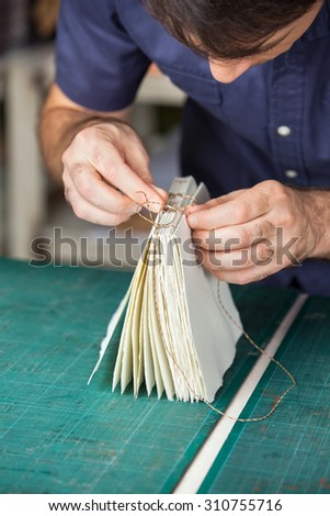 Mid adult male man binding pages at table in paper factory - stock photo