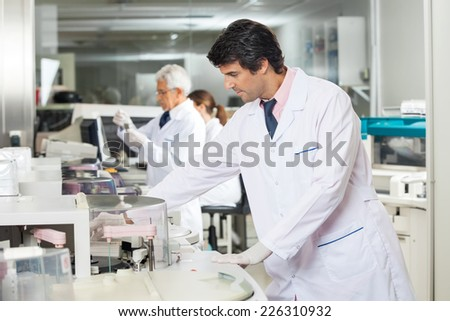 Mid adult male technician experimenting in laboratory using centrifuge - stock photo