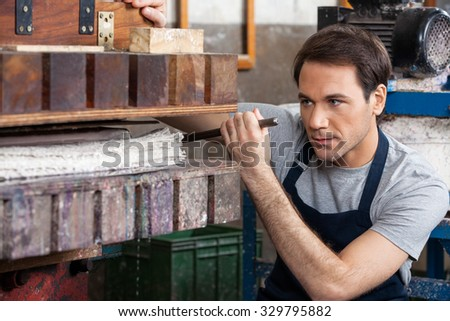 Mid adult male worker looking at papers in press machine at factory - stock photo