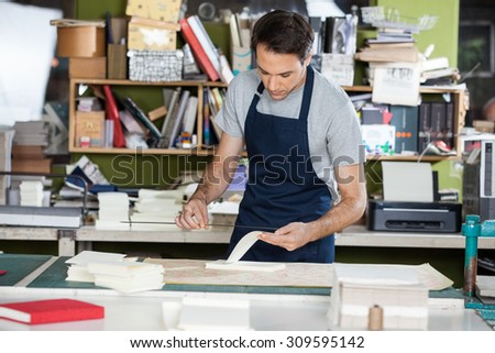 Mid adult male worker working at table in paper industry - stock photo