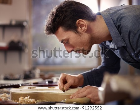 mid adult man at work as craftsman in italian workshop with guitars and musical instruments, smoothing guitar body - stock photo