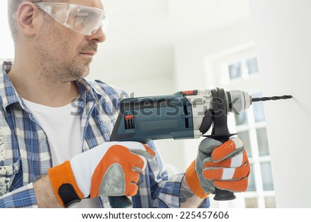 Mid-adult man drilling hole in wall - stock photo