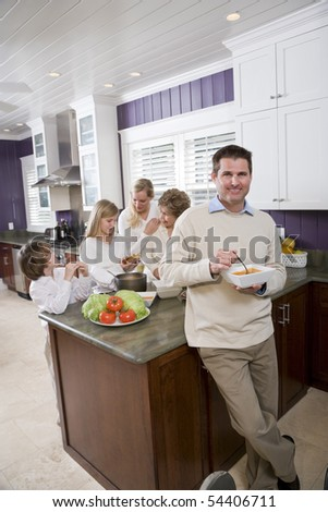 Mid-adult man eating lunch in kitchen with family in background - stock photo