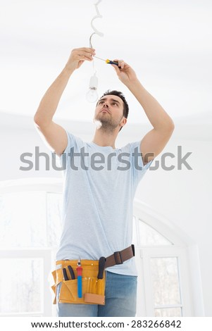 Mid-adult man fixing light bulb wiring in new house - stock photo