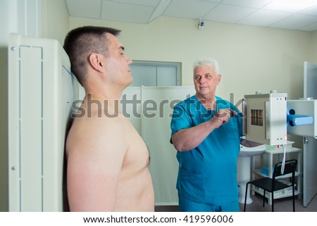 Mid adult man patient  mature male doctor setting up the machine to take x-ray - stock photo