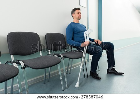 Mid-adult Man Sitting On Chair With Crutches In Hospital - stock photo