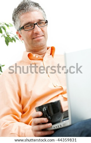 Mid-adult man sitting on couch, drinking coffee, browsing internet on laptop computer. Isolated on white.