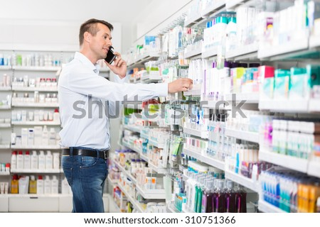 Mid adult man using mobile phone while selecting product in pharmacy - stock photo