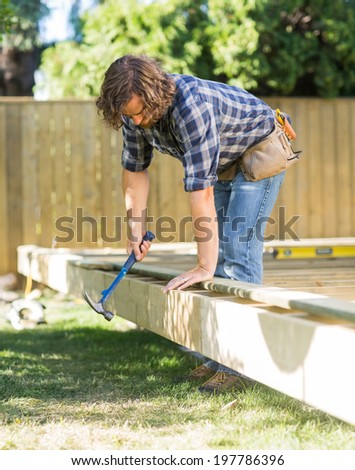Mid adult manual worker using hammer on wooden frame at construction site - stock photo