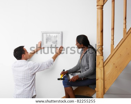 mid adult multiethnic couple hanging pictures to the wall and smiling. Horizontal shape, copy space - stock photo