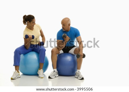 Mid adult multiethnic man and woman balancing on blue exercise balls while working out with dumbbells. - stock photo