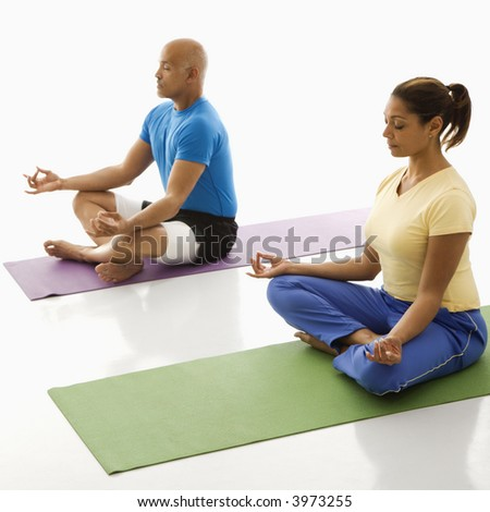 Mid adult multiethnic man and woman sitting in lotus position on exercise mats with eyes closed and legs crossed. - stock photo