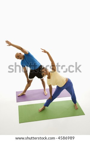Mid adult multiethnic man and woman standing on exercise mats with arms extended overhead stretching. - stock photo