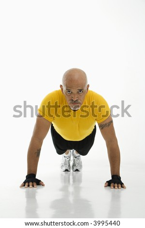 Mid adult multiethnic man wearing yellow exercise shirt doing pushups while looking at viewer. - stock photo