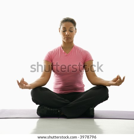 Mid adult multiethnic woman sitting in lotus position on exercise mat with eyes closed and legs crossed. - stock photo