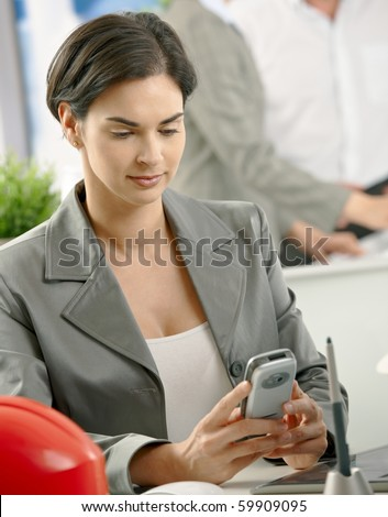 Mid-adult smart professional sitting in office using pda, smiling.? - stock photo