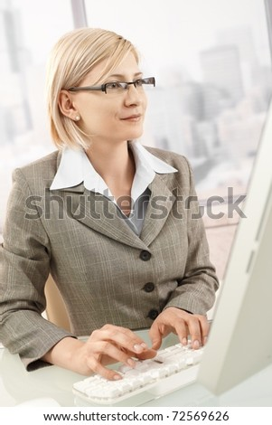 Mid-adult smiling businesswoman sitting at work, using desktop computer, typing on keyboard.?