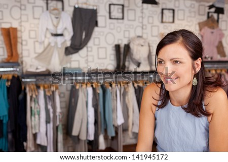 Mid adult smiling woman in clothing store - stock photo