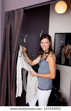 Mid adult smiling woman looking in camera while standing in changing room
