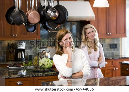Mid-adult woman and teen daughter standing in kitchen - stock photo