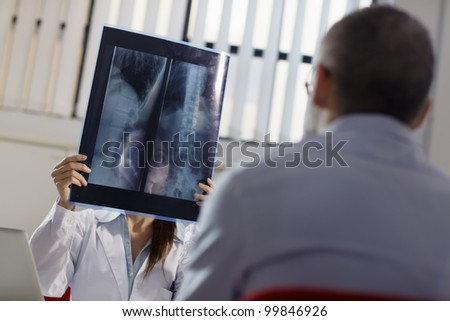mid adult woman at work as doctor in office and examining x-rays with patient - stock photo