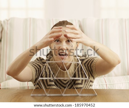 Mid-Adult Woman Building House of Cards - stock photo