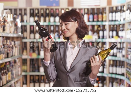 Mid Adult Woman Choosing Wine in a Liquor Store - stock photo