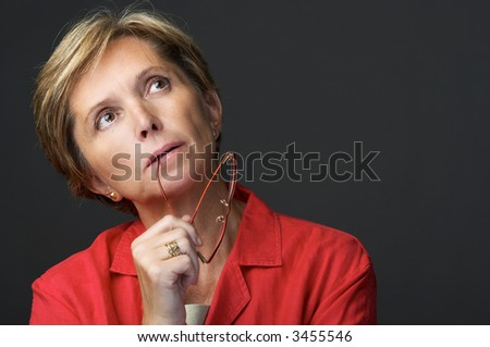 Mid adult woman contemplating. Isolated on grey. - stock photo