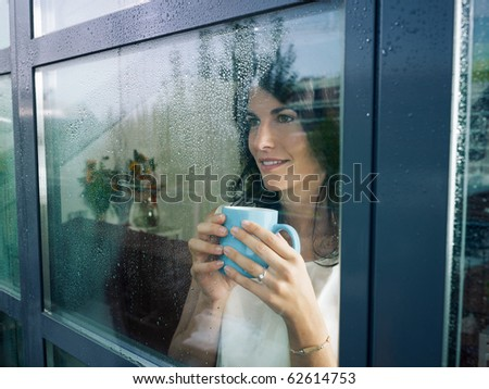mid adult woman drinking coffee and looking out of the window on rainy day. Horizontal shape - stock photo