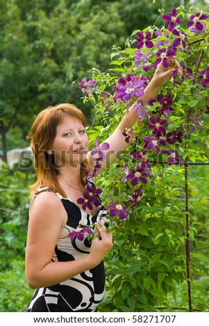 Mid adult woman gardener with  clematis in summer - stock photo