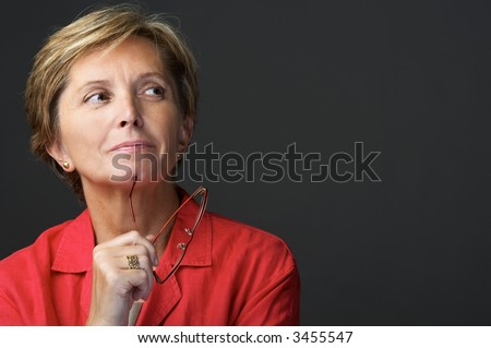 Mid adult woman holding glasses and looking sidewards - stock photo