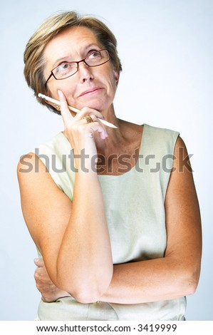 Mid adult woman holding pencil looks above with curiosity, studio shot. - stock photo