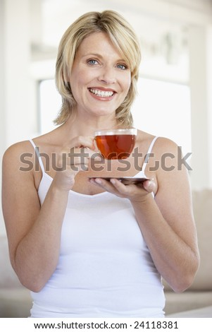 Mid Adult Woman Holding Tea Cup And Smiling At Camera