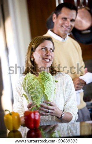 Mid-adult woman in kitchen with husband standing behind - stock photo
