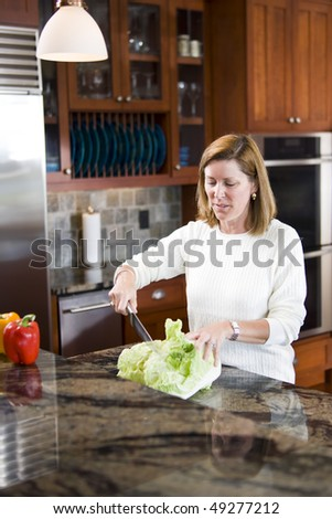 Mid-adult woman in modern kitchen slicing vegetables with knife on counter - stock photo