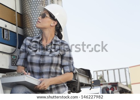 Mid adult woman inspecting timber truck - stock photo