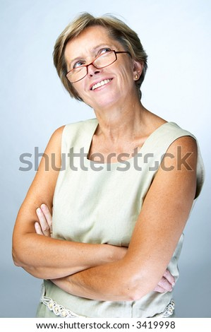 Mid adult woman looking up with her arms crossed, studio shot. - stock photo