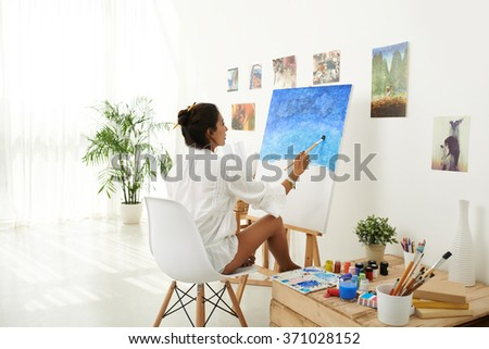 Mid adult woman painting at her home art studio - stock photo