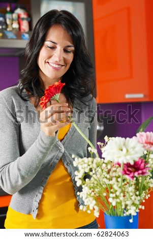 mid adult woman putting gerbera in blue pot. Vertical shape, front view, waist up - stock photo