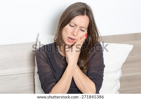 Mid-adult woman sitting in bed with toothache - stock photo