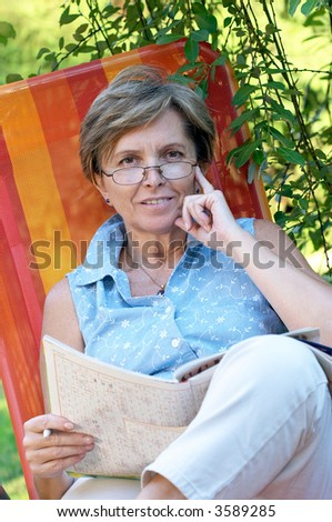 Mid adult woman sitting on a reclining chair - stock photo