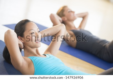 Mid adult woman smiling while doing sit-ups at gym with female friend in background - stock photo