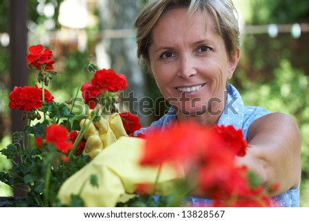 Mid adult woman taking care of flowers, portrait - stock photo