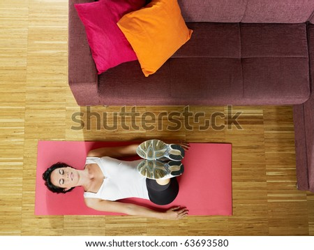 mid adult woman with legs raised training abdominals at home. Horizontal shape, full length, front view, copy space