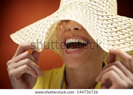 mid adult woman with straw hat smiling and having fun on red background - stock photo