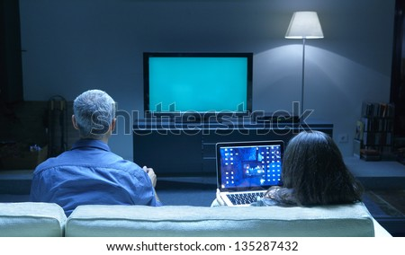 Mid Adults watching TV and PC blue tone - stock photo