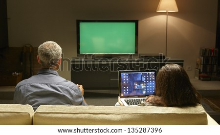 Mid Adults watching TV and PC thanks to Internet possibilities - stock photo