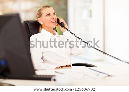 mid age businesswoman talking on the phone in office - stock photo