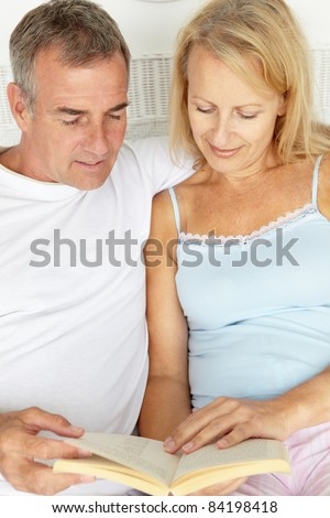 Mid age couple reading together - stock photo